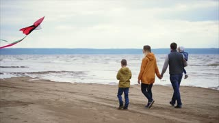 Happy family walking along the shore. Man, woman, little boy and girl playing with kite on the beach. Windy cold weather