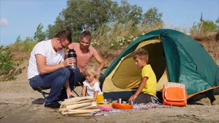 Happy family with two children enjoying camping trip. They having picnic near the tent and kids want some tea