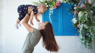 Happy mother holds her little child on hands indoor. She throws her up in the air and they laughs together. Mom kisses her in the cheek.