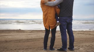 Happy young family. Man with woman and little girl standing on the ocean shore and lookin on horizont