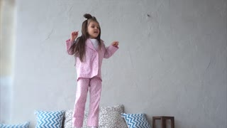 Happy young girl having fun in bedroom. Jumping and playing on bed. Girl in pink pajama.