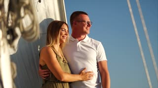Happy young loving couple having relaxing sea trip on the yacht. Traveling under sail