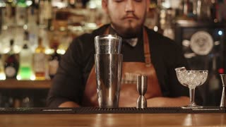 Hipster bartender is working in a cafe mixing cocktails at the bar. He is holding a bottle of syrup and pouring.