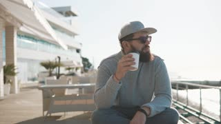 Hipster man with beard is enjoying cup of coffee in morning near ocean. He is sitting crossed legs on a bench in open air veranda of restaurant