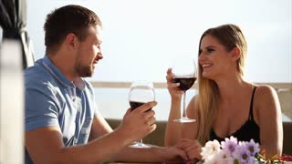 Husband is proposing a toast for his beautiful wife on outdoor restaurant terrace near the sea. They are drinking red wine and lovely spending their day.