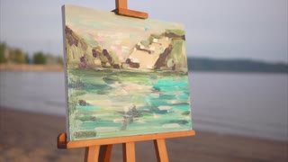 Impressionism style painting with landscape on easel. Canvas executed in oil against nature background