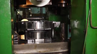 Industrial press machinery is shaping steel plate to part of wheel. Sheets are fed manually, close-up shot.