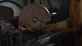 Industrial worker is using big grinding machine to smooth edges of a metal tube. Sparks are popping off the metal tube.