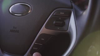 Interior of the car. Man controls the modes of music in car on steering wheel.