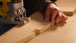 Joiner is carving slots in wood board in workshop. He is using small hand-held jig saw, directing it over plank