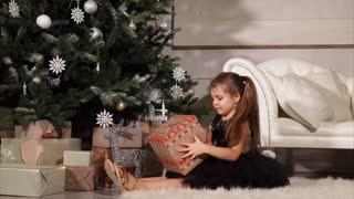 little girl in a smart dress twists in her arms box with a Christmas present, she sits on the floor near a tree decorated with garlands, the beautiful woman wants to understand what she will be given
