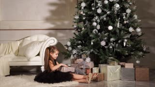Little girl is happy to get the gift. She sitting on the floor with present near Christmas tree
