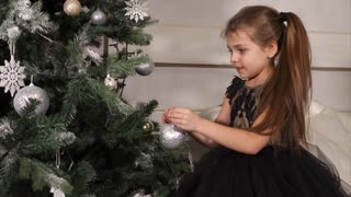 Little girl preparing for holiday and decorating Christmas tree with glittering silver ball