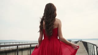 Lovely brunette woman is enjoying her day walking on the shore alone. She is wearing nice red dress.