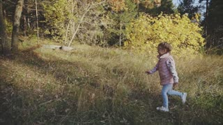Lovely kid is running towards her mother in the meadow during the fall. She jumps on mother's hands and she catches her.