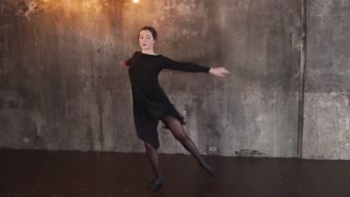 Lovely woman does dancing show alone in a stylish studio. She is dancing with a wall with shining light bulbs on a background.