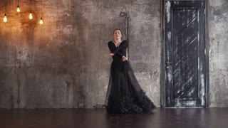 Lovely woman slowly dancing in her black dress alone against concrete wall and old door. Showing passion and love.