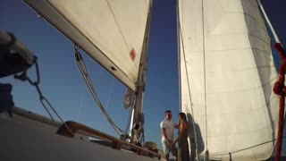 Low angle shot of yacht with loving couple standing under sail. Romantic sea trip