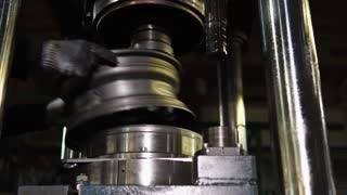 Machine operator is putting metal blank of wheel under press and removing done, putting other. Pressing workshop on an industrial plant of production of steel wheels.