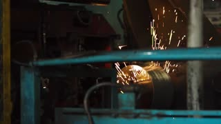 Machine welding system is making joints on circular steel sheets. Bright sparks are flying on sides, production of steel wheels.
