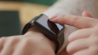 Macro shot of a young woman's hands, who uses a new gadget - a smart watches. She likes the new device, which simplifies work with smart technology.