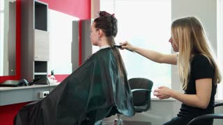 Making stylish hairstyle in fashionable beauty salon. Female customer and female hairdresser. Customer covered with cape