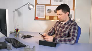 Male manager using smartphone to talk with his client or for other working needs. Classical office scene.