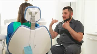 male orthodontist is conducting a primary consultation for a woman who came to the oral cavity. A young woman wants to get rid of tooth decay in a dental hospital where there are professional doctors