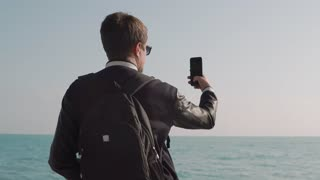 Male tourist is watching seascape and filming video using his mobile phone. He is standing back and holding gadget in hands, moving it in air