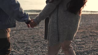 Man and woman are holding hands and moving to sea over gravel beach. Back view and close-up of hands, happy loving pair