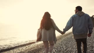 Man and woman are holding hands to each other and strolling on sea coast in evening. Loving pair is meeting sunset in romantic walking