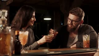 Man and woman spend time in a bar drinking shots together. Friends enjoying company of each other.