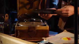 Man cleaning dust from the vinyl record and putting it on the gramophone. Retro music