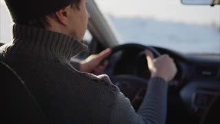 Man driving a car on the winter road.