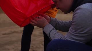 Man igniting the candle in sky lantern. Preparation of launching of the sky lantern.