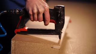 Man in a carpentry workshop using air pumped staple gun. He is stapling plywood along the straight line to the construction.