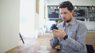 Man in casual wear sitting in the cafe. He using his smartphone while waiting for an order