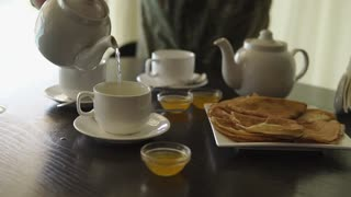 Man is pouring tea in a cups sitting at the table. Morning food. Pancakes and honey on the table.