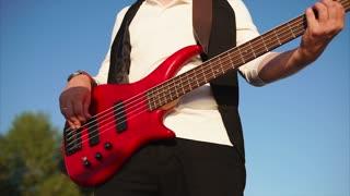 Man musician playing bass guitar during band performance outdoor