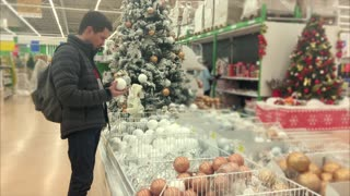 Man preparing for Christmas and New Year holidays. He buying decorations in the hypermarket