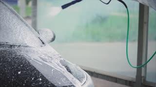Man spraying chemical vehicle cleaner foam on his car. Car wash self-service. Car washing.