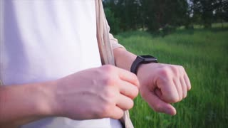 Man using smartwatch. He typing and selecting settings on it. Close up view. Technologies in our life
