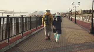 Man with her girlfriend is walking in evening over quay. They are dressed in velvet funny costumes and coats, holding hands, back view