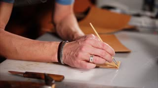 Man works with brush to put glue on the piece of leather. He carefully puts layer by layer leaning on the table.