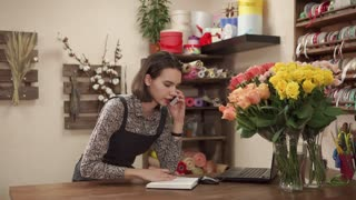 Managing director woman of floristic shop is calling by mobile and doing notes in a book. She is accepting orders from customers on a delivery of flowers