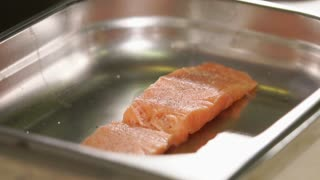 Marinating of fish filet by lemon juice in a restaurant. Liquid is falling on a surface of salmon before baking, close-up
