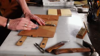 Master is cleaning his leather product from glue and production dust. Custom manufacturing of leather haberdashery, hand made and unique luxury accessories.