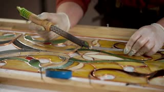 Master is using a soldering iron for decorating and processing frame of stained-glass picture. He is melting tin and applying it on copper base.