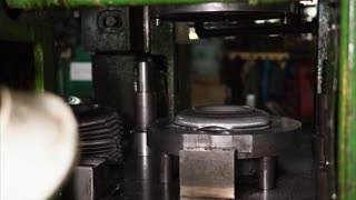 Molding of parts of wheels by press in automobile factory. Worker is commanding tool and changing blanks under press by hand.