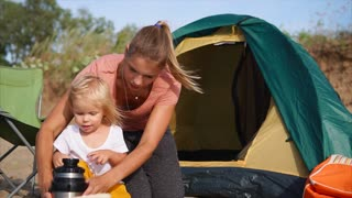 Mom and little daughter pouring hot tea from thermos jug being on picnic in the countryside. Family camping with tent